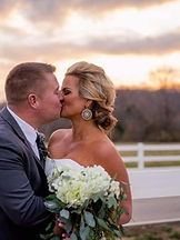 couple kissing with farm in background at Brookdale Farms