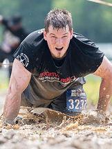 Crusher race participant crawling in mud