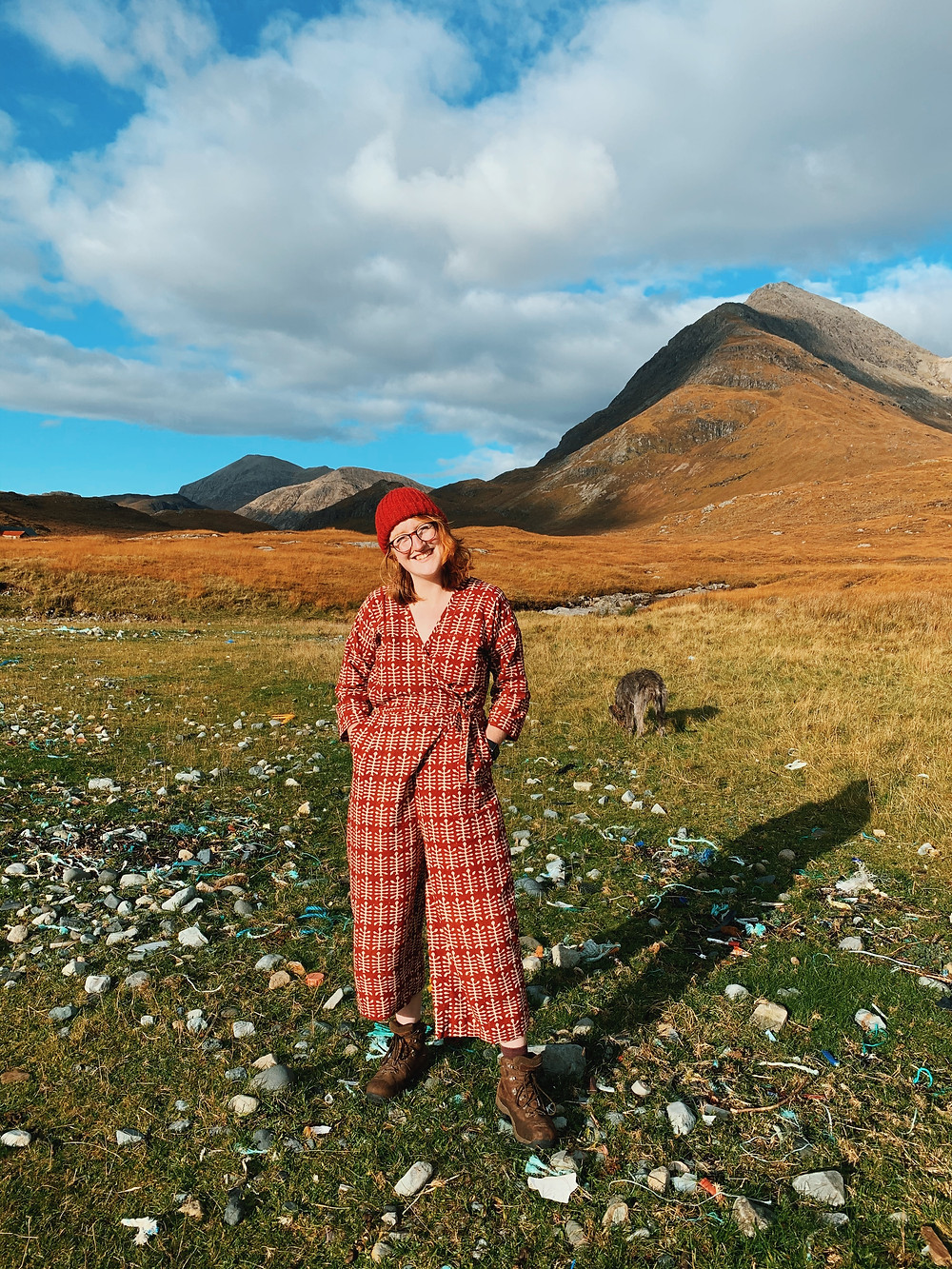 [Picture 4 - Roisin wears a Zadie Jumpsuit, made from second hand fabric and stands in a wide Scottish Landscape, all the colours of autumn. She wears a bright red wool hat and walking boots.]