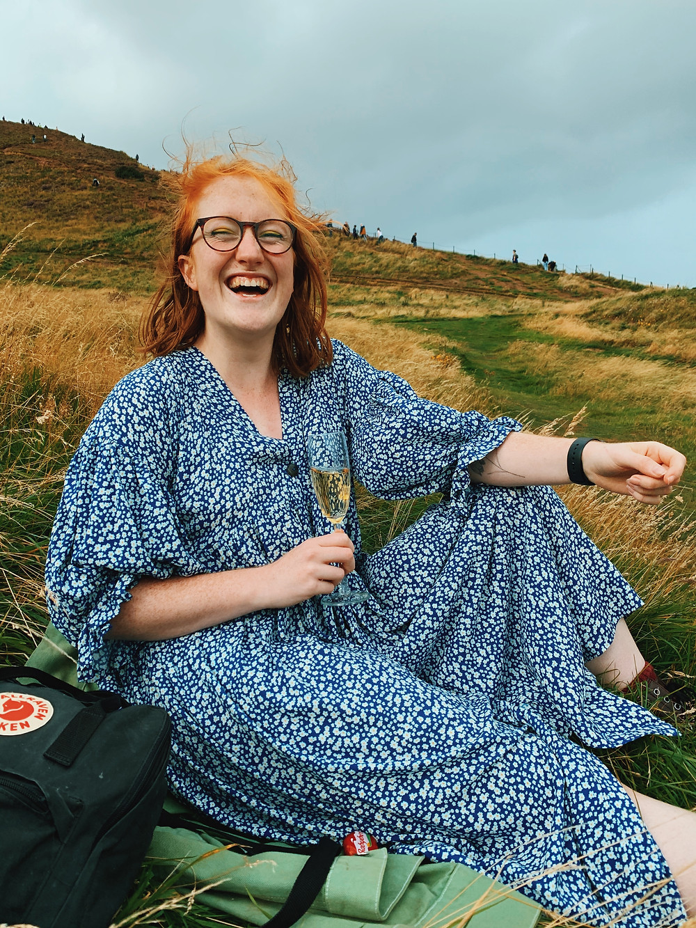 [Picture 7 - Roisin wears a Birgitte Helmersson Zero Waste Gather Dress made in a blue daisy print viscose from Sister Mintaka, she is laughing and sitting on the top of Arthur's Seat drinking prosecco in Edinburgh]