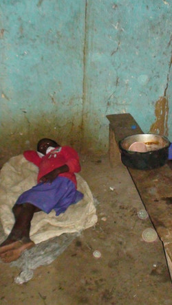 A child in East Uganda sleeps on the cold hard floor w paper thin mats and plast