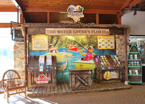 Mural and display of people canoeing on a crystal blue river