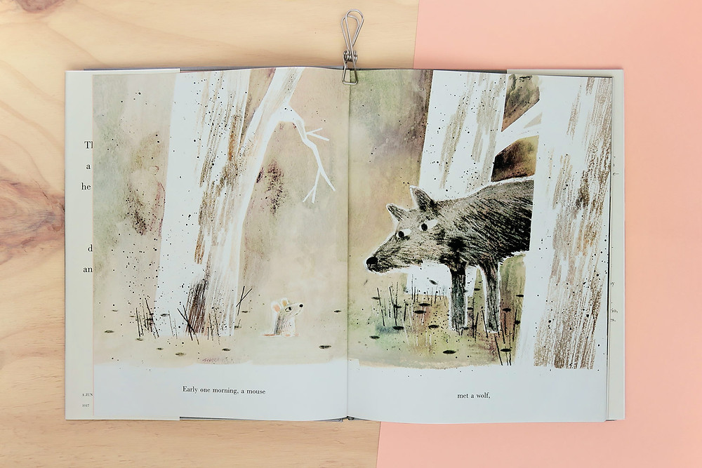 Photo of page spread of picture book with a wolf and a mouse in a forest