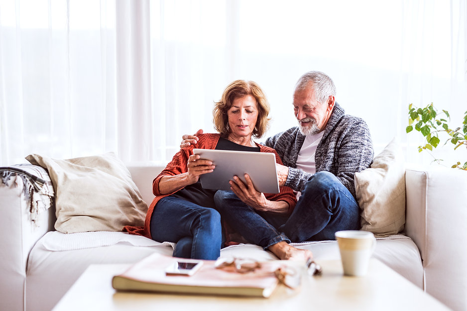 senior-couple-with-tablet-relaxing-at-ho