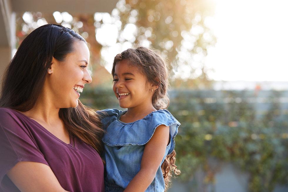 smiling-hispanic-mother-holding-daughter