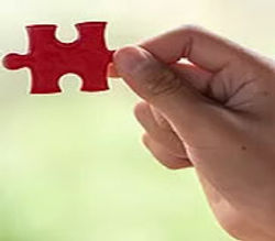 hands-holding-piece-of-red-jigsaw-puzzle