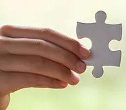 hands-holding-piece-of-beige-jigsaw-puzz
