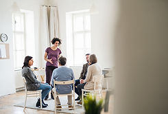 Young woman standing and talking to other people during group therapy. by Jozef Polc on 500px.com