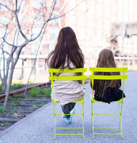A woman and a child sitting in a park in bright green chairs with their backs facing the camera.