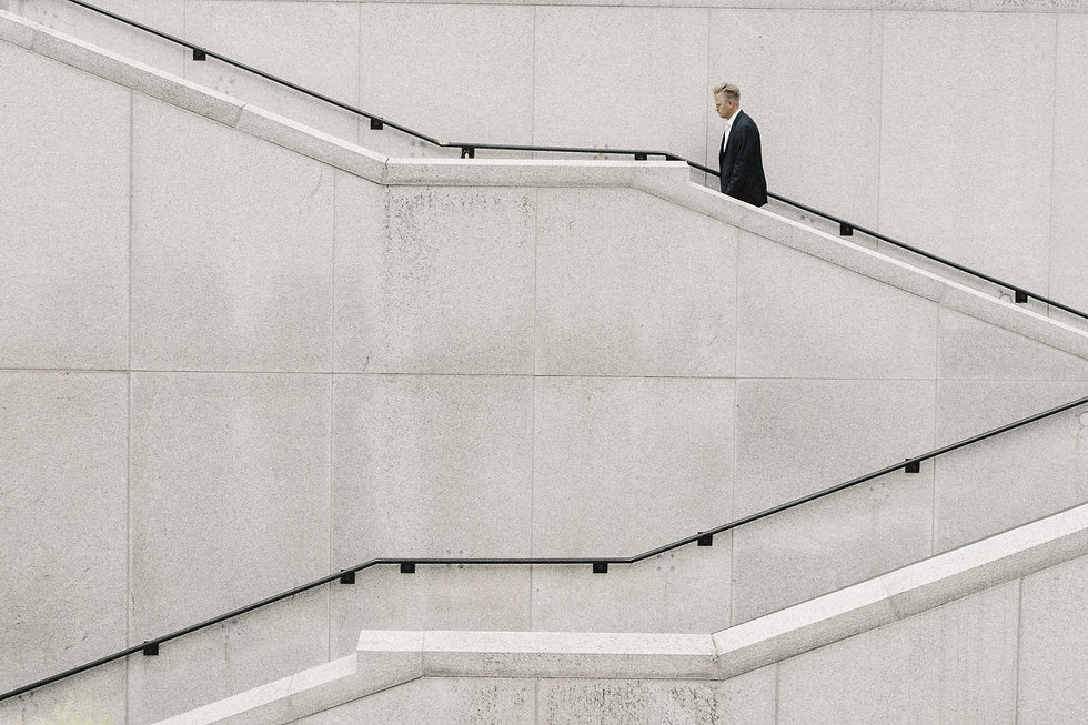 man in a black suit walking on grey staircase
