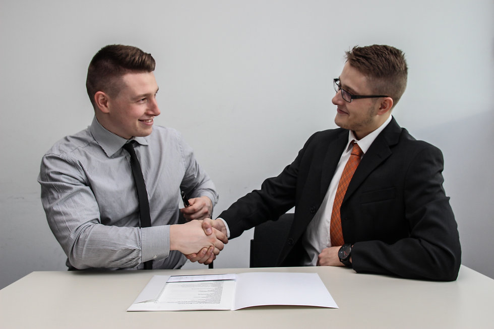 two men shaking hands and signing a deal