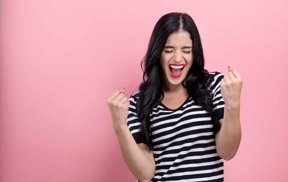 Happy young woman making a yay gesture o