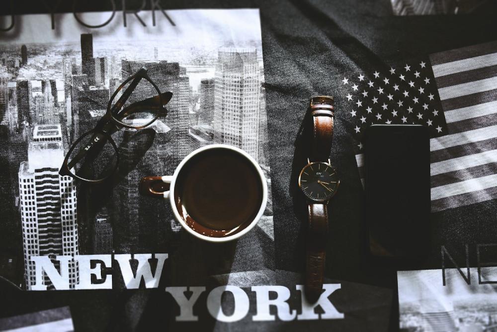 Kubek kawy, okulary, zegarek, telefon i amerykańska flaga. W tle napis New York