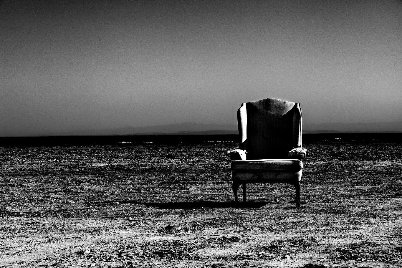 Lone vintage armchair on the beach along