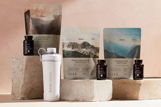 A selection of Form Nutrition Products on top of bricks and against a stone coloured background. The products include their superblend protein, performance protein, pureblend protein, boost capsules, ZZZZs capsules and Edge Capsules, including Form Insulated Stainless Steel Shaker.