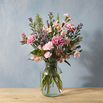A picture of the Jules bouquet from Bloom & Wild of pink and lavender flowers in a vase.