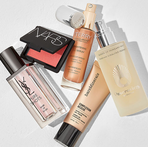 A selection of make up including YSL Pure shots in a pink bottle, NARS blusher, Terry Brightening Serum, Bare Minerals Complexion Rescue and Omorovicza Mist.
