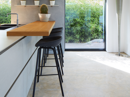 A kitchen design with a polished concrete floor
