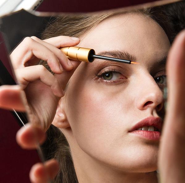 model applying eyelash growth serum