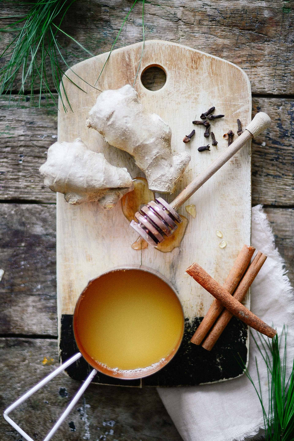 cutting board, rustic, pineapple, ginger, honey, cinnamon sticks, warm winter drink, black pepper
