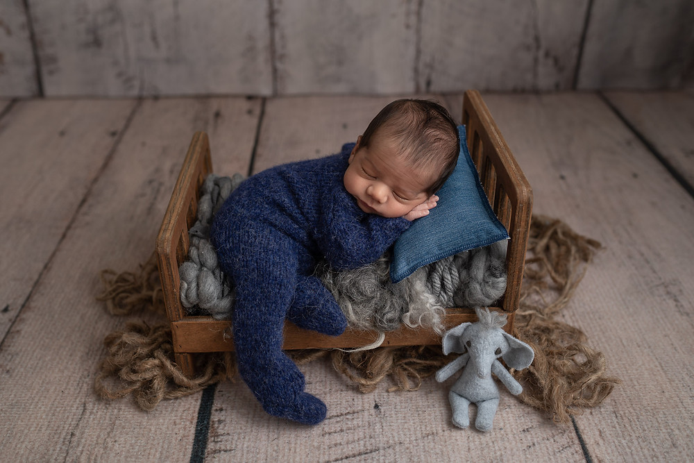 Baby boy Kaveh, wearing blue romper and laying on a bed and posed with tiny elephant