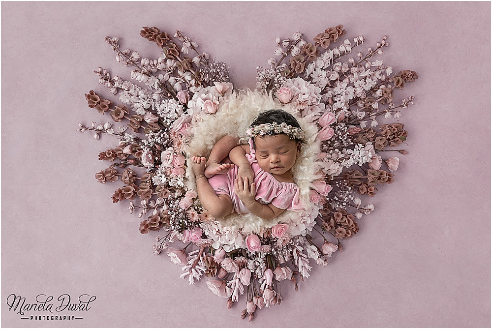 Baby girl laying in a heart of pink flowers wearing a pink romper. Newborn photography picture ideas in pink