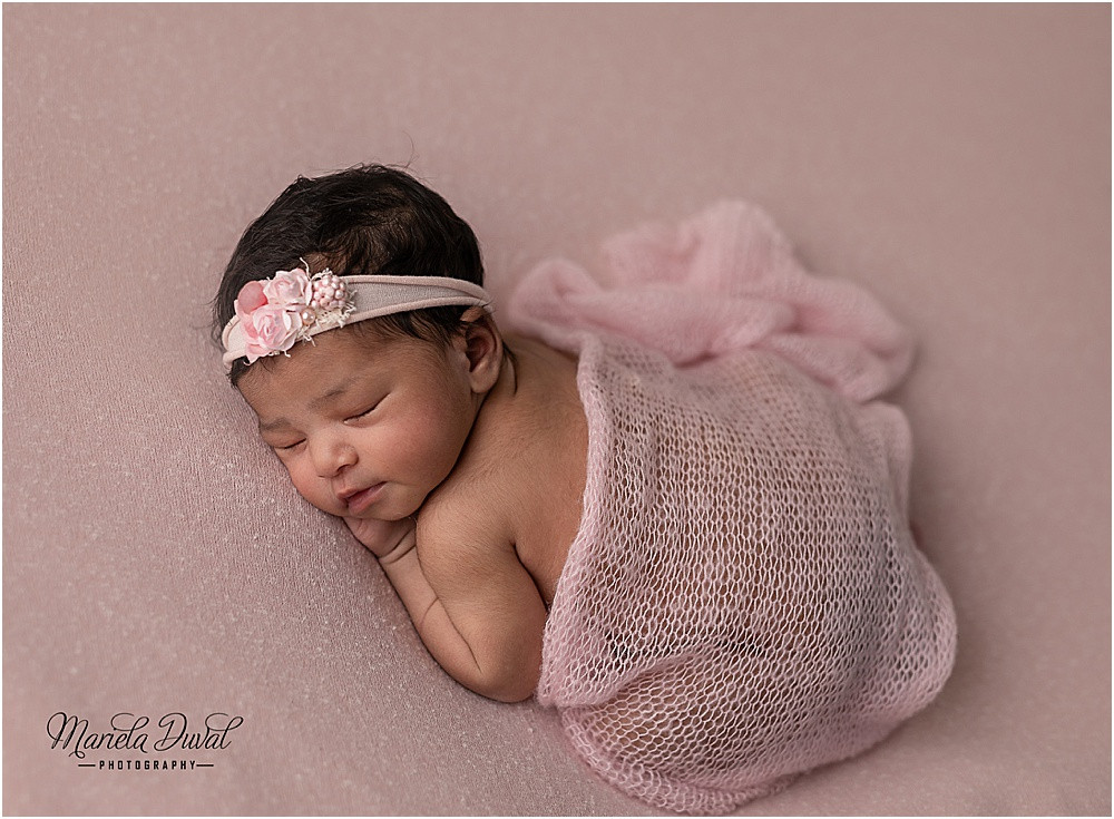 Baby girl in pink covered by a knit layer laying on her tummy- picture captured by Mariela Duval Photography