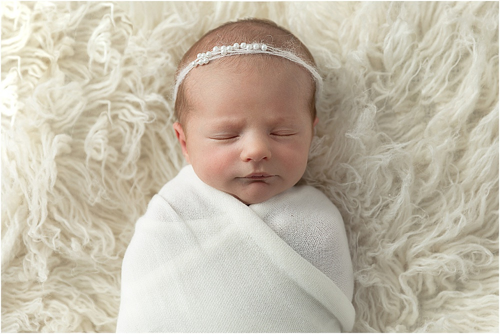 Newborn baby girl in cream background photographed by Mariela Duval Photography in Atlnta Georgia