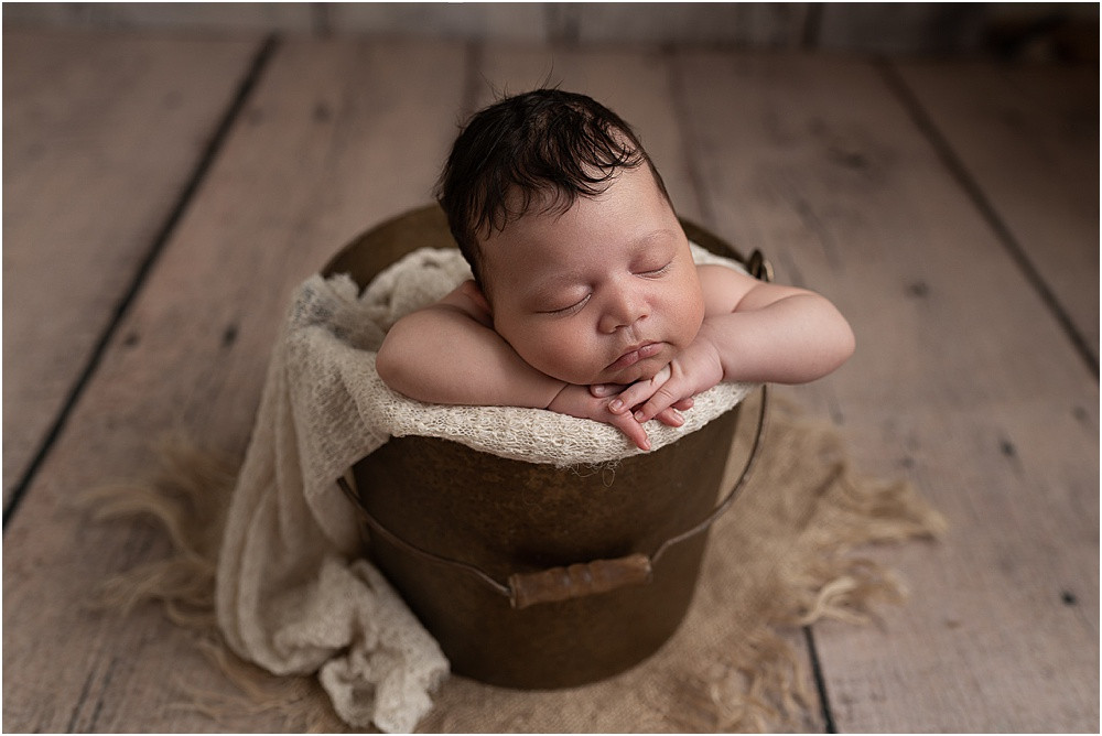 baby boy posed inside a bucket and with chin on his hands