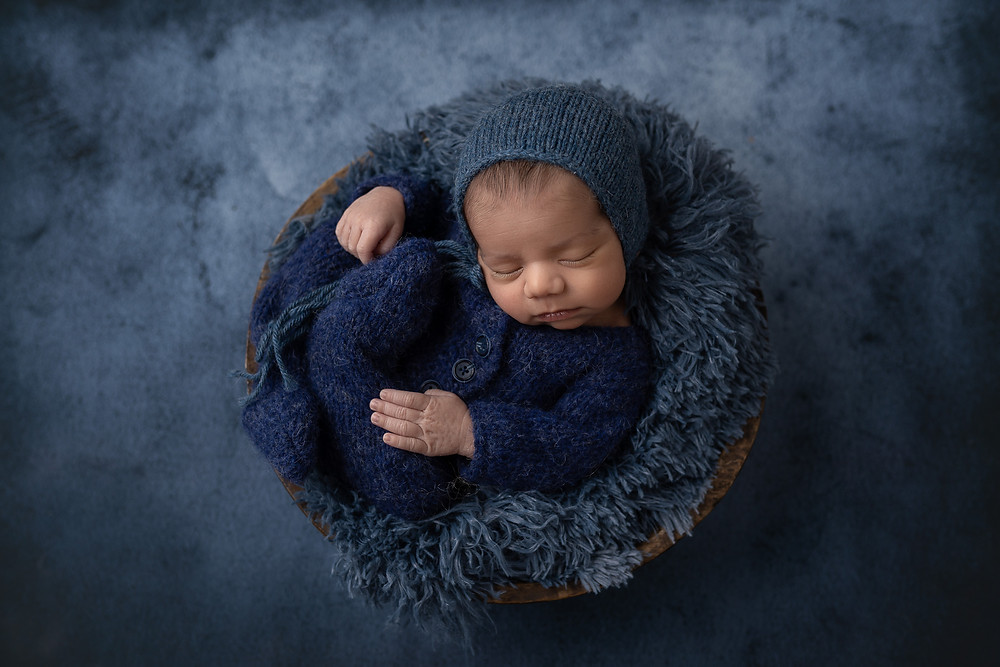 Baby boy wearing a navy outfit, posed inside a  bowl and hat and laying on a dark blue background