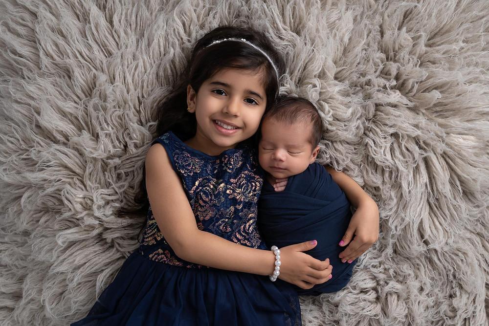 big sister and baby brother laying on grey flokati