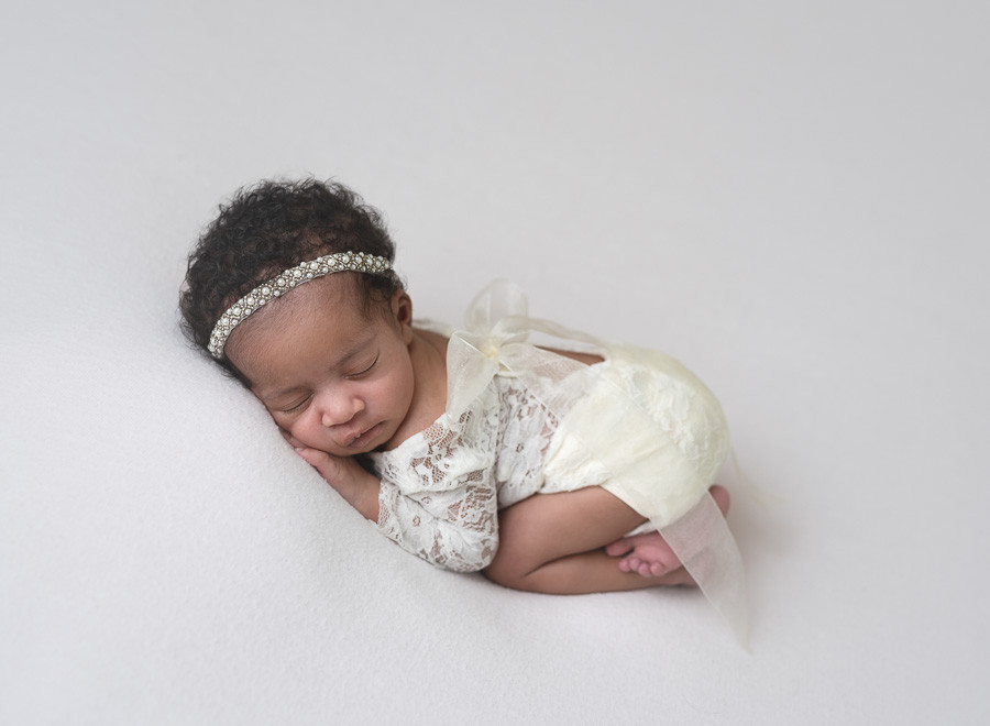 baby girl wearing a lacy romper and pearl headband on a white background