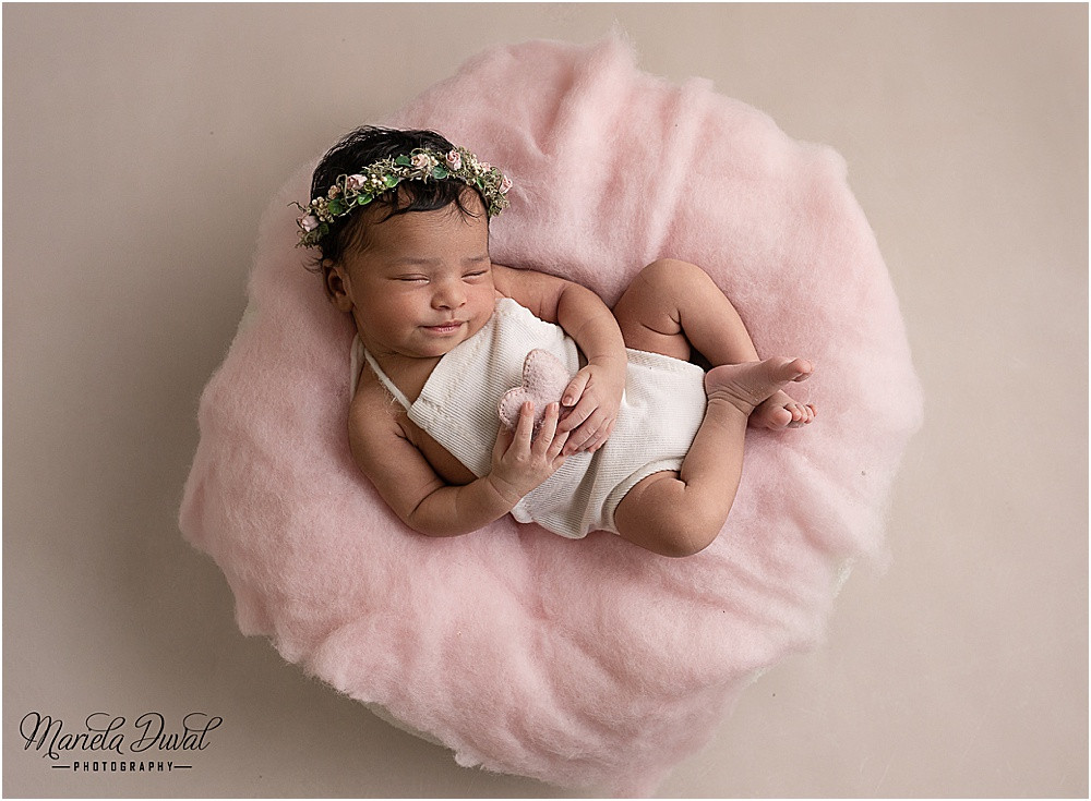 Baby girl laying in a pink fluff holding a heart and a most beautiful smile, taken at home studion in Sandy Springs, GA