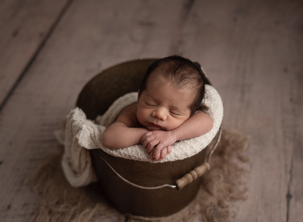 Baby boy posed inside a brown bucket with cream color layer.  Image taken by Mariela Duval Photography