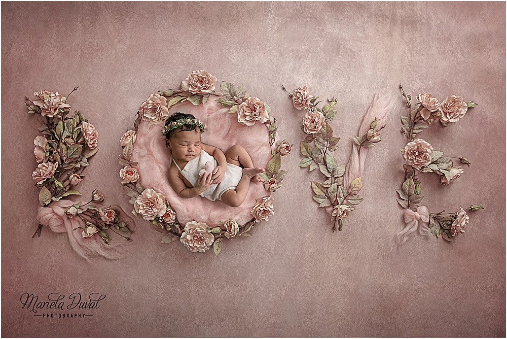 Newborn girl laying in a fluff of pink surrounded by flowers and scarfs that spell the word LOVE