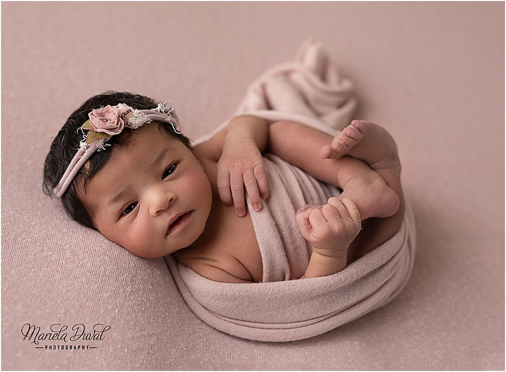 Newborn baby girl, 8 day new, wrapped in pink and having great contact with camera- image captured in our home studio in Dunwoody/Sandy Springs