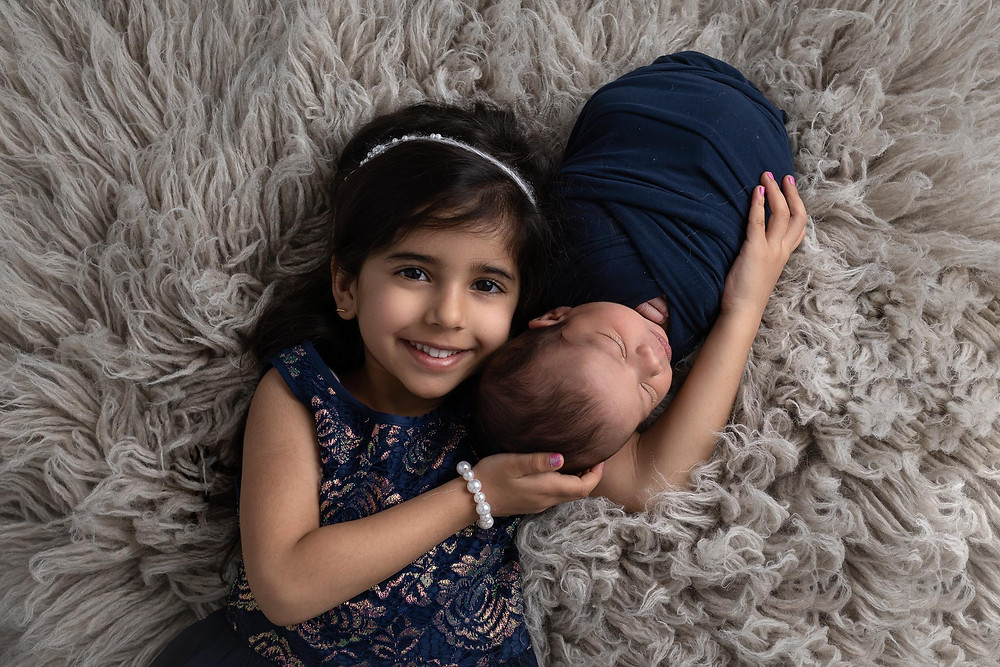 Big sister holding baby brother, both wearing navy blue and laying on grey flokati.  Image taken by Mariela Duval Photography