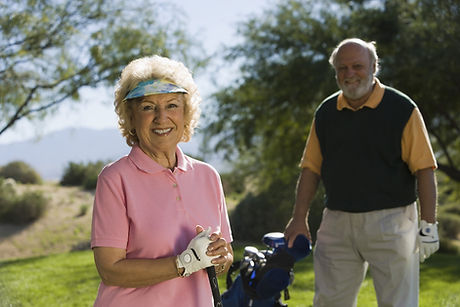 Portrait of a female golfer with man standing in background.jpg