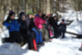 students sitting on a log in a snowy forest