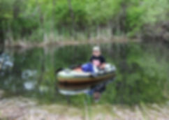 student in boat on pond