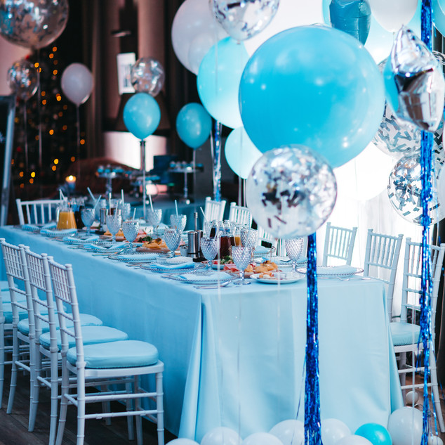 Blue white and silver balloons hang over
