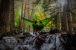 couple relaxing in a forest on a hammock strung over a creek - Photo Credit: Spring Fed Images via Unsplash