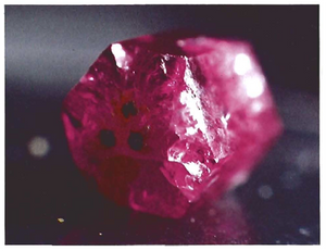 Three Bixbyite on a Red Beryl Termination from Gems & Gemology Winter 1984