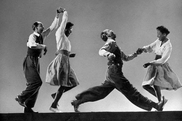 Two dance couples dance the Lindy Hop in a vintage black and white photo