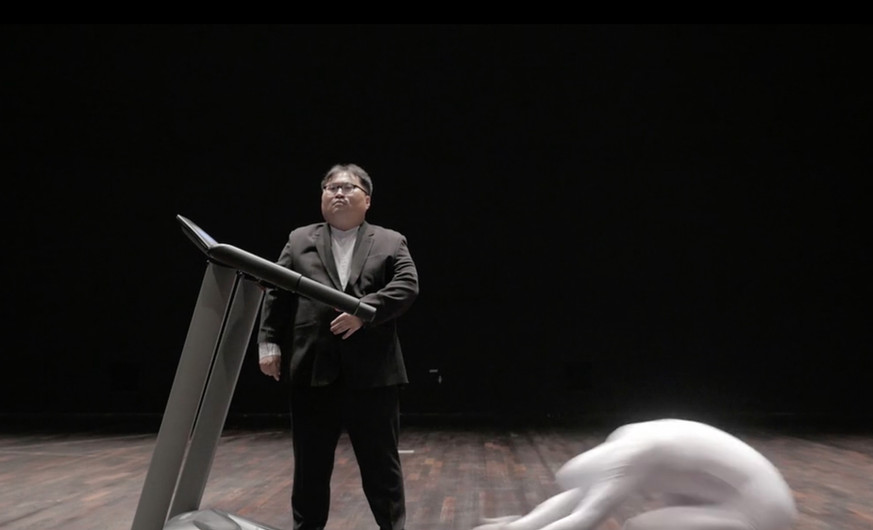 """Oak Jungho (b.1974) The Noble Spirit: Three Steps One Bow 2016 Video With humor and absurdity, the artist performs the """"three steps one bow"""" Buddhist ritual prostration in such a way to demonstrate the futility of one's actions. Despite Oak Jungho's efforts, he is never able to keep with the ever-increasing speed of the treadmill manipulated by a suited authority figure. In the context of the broader Korean society and the Candlelight protests, Oak's anonymized body—clothed in a white jumpsuit—is a stand-in for the poor and helpless in modern Korean society."""