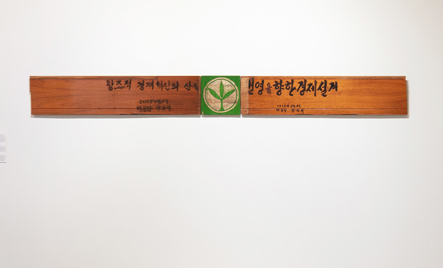 """Kim Jongku (b.1963)  Green Plant 2019 Triptych (plywood wall panel, iron powder, PV glue, acrylic paint)  This triptych combines three elements associated with former South Korean presidents Park Chung-hee and his daughter Park Geun-hye. The Saemaeul-ho Undong (New Community Movement) was a political initiative launched in 1970 by Park Chung-hee to modernize the rural South Korean economy. According to Kim, the green plant logo on the Saemaeul-ho Undong flag, which both Park Chung-hee and Park Geun-hye stood behind, is a decoy to conceal the two policians' shortcomings. In this work, the Saemaeul-ho Undong green plant is replaced by another """"green plant""""—marijuana—calling attention to the hallucinogenic effect of the political symbol.   """"Blueprint for economic success."""" – Park Chung-hee """"Result of economic innovation."""" – Park Geun-hye  Written in iron powder, the artist replicates the calligraphy of President Park Chung-hee and his daughter Park Geun-hye. Enlarged and solidified through Lee's signature medium, the bombastic slogans seem ironic and out of place. As Kim explains, the word huiho means """"wielding a brush."""" This calligraphic work symbolizes wielded power through nepotism, and the abuse of power in the name of """"economic development"""" and """"anti-communism."""" Impeached president Park Geun-hye is the daughter of former president Park Chung-hee, who initially ruled South Korea as a military dictatorship before becoming its president in 1963. He was assassinated in 1979 by a friend and member of his regime."""