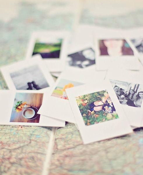 Polaroid photos in a pile on a map