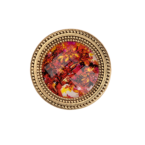 golden magnetic pin with red floral imagery under a faceted crystal