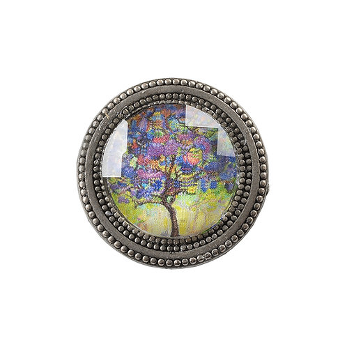 golden magnetic pin with painting of a tree in purple and yellow under a faceted crystal