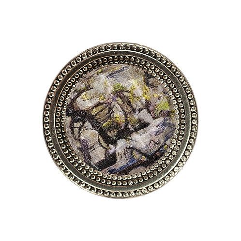 golden magnetic scarf pin with tree imagery in neutral color palette under a faceted crystal